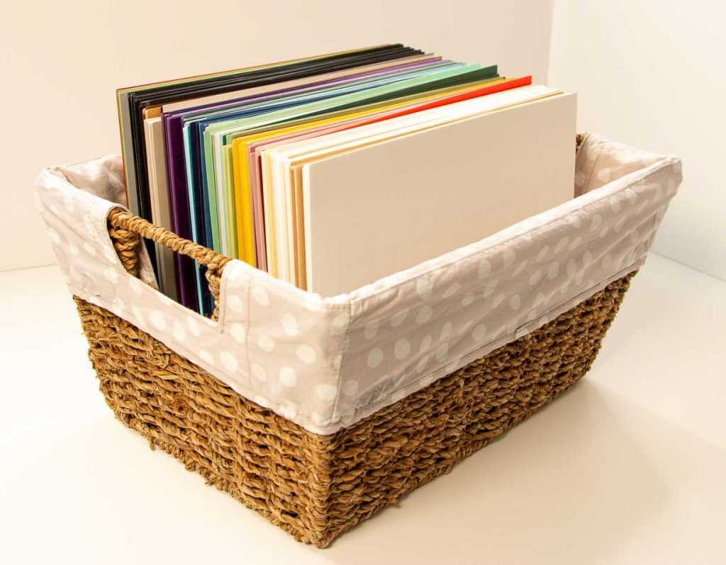 Fabric lined wicker basket with colorful cardstock standing on end.