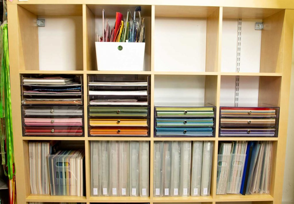 Cubed style bookcase with paper in acrylic drawers, bins and plastic files