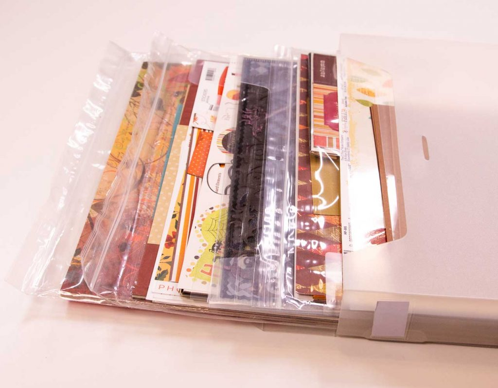 Patterned scrapbook paper stored in clear plastic bags and clear paper files