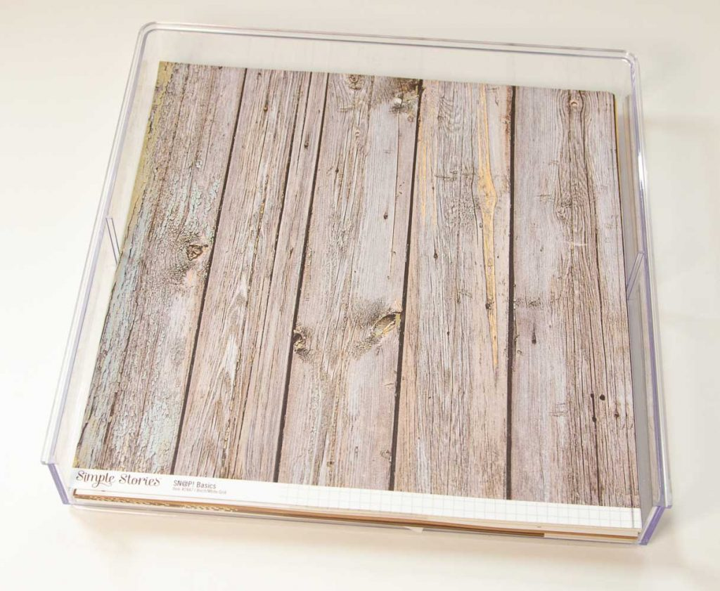 Clear acrylic paper tray that is 12x12 filled with paper with a wood pattern