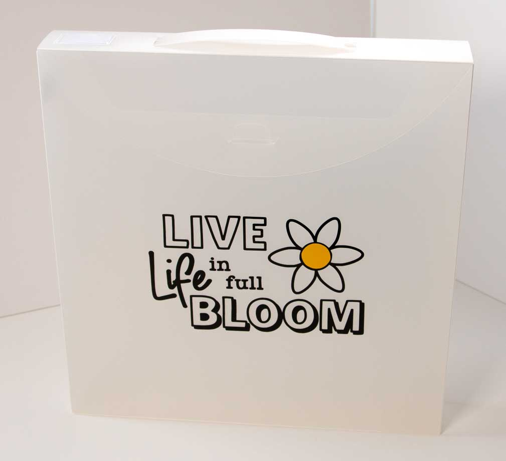 12x12 plastic case with the saying Live Life in full Bloom and a daisy on the front. It holds 12x12 papers.