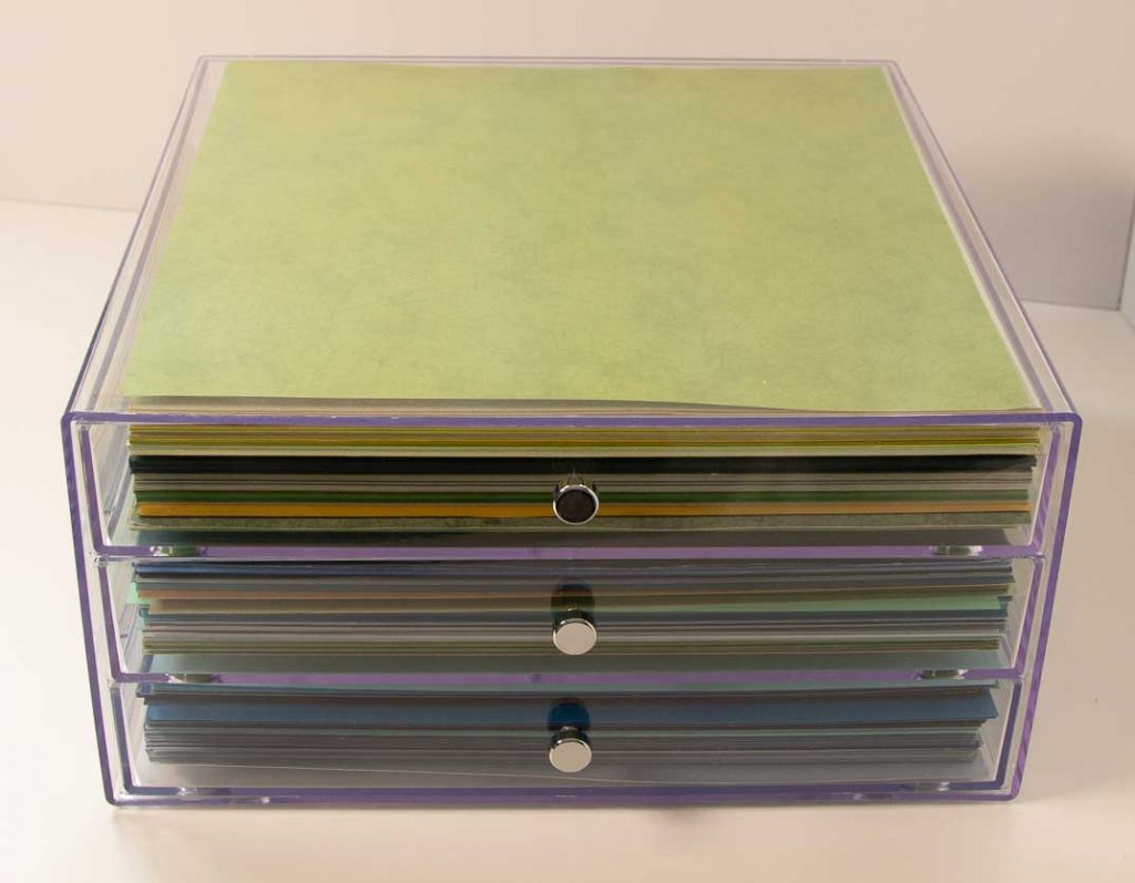 Clear acrylic 3 drawer organizer filled with colored sheets of paper