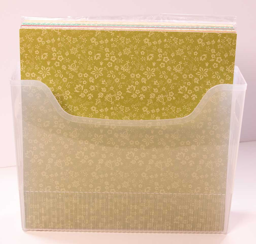 Semi clear plastic bin with an open top and 12x12 patterned paper inside